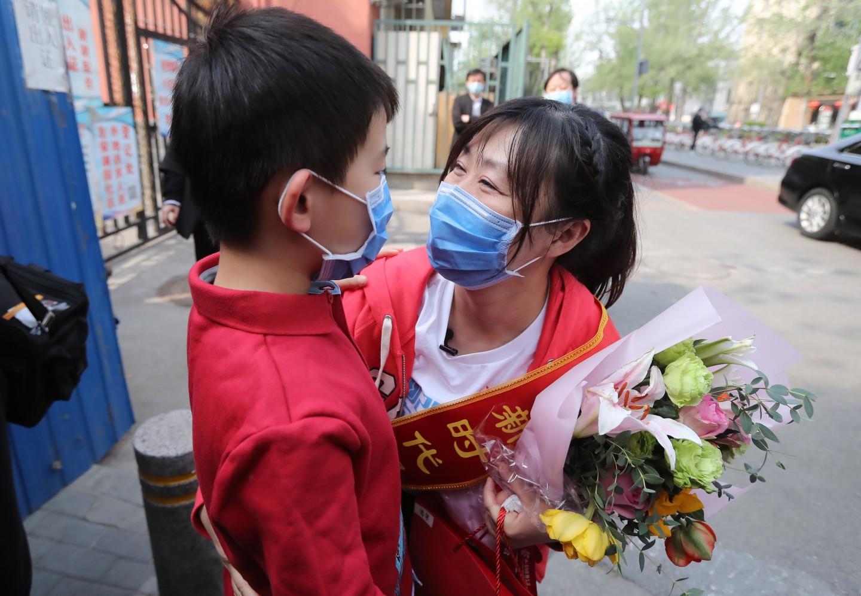"""医疗队员潘攀与儿子团圆。孩子抱着潘攀说:""""妈妈我为你自满。""""新京报记者 王贵彬 摄"""