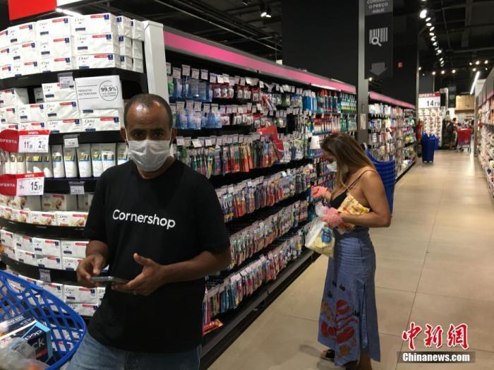 当地时间4月9日,在巴西圣保罗,民众戴着口罩在一家超市购物。