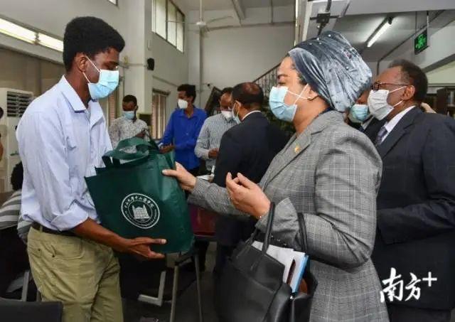 """非洲国度驻穗领团团长、马里驻穗总领事艾丽玛·加库(右)向非洲国度留学生送""""康健包""""。"""