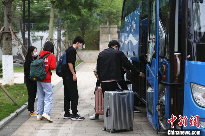 学生将行李拿下车。 朱柳融 摄
