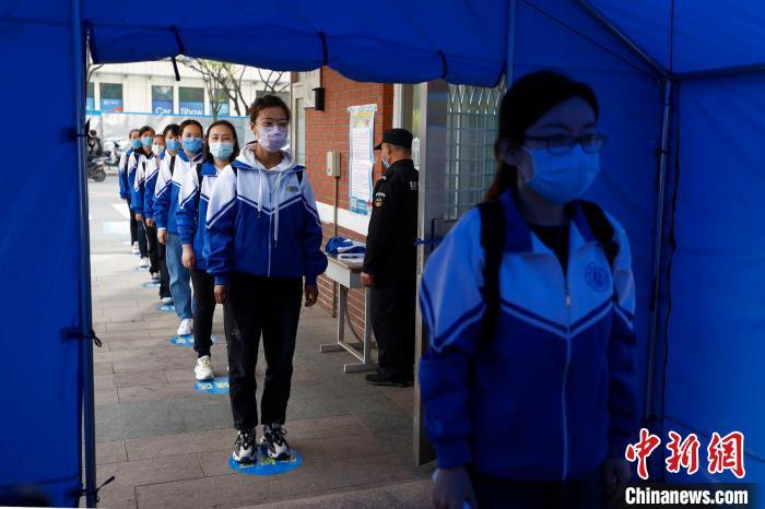 """跟着北京市高三年级开学日期邻近,各中学演练中做好战""""疫""""预备。图为北京十二中举办一场全流程的开学模仿演练。中新社记者 富田 摄"""