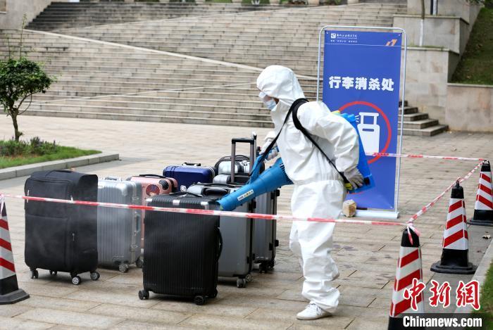 工作人员正在对学生的行李进行消杀。 朱柳融 摄