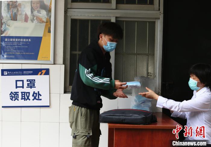宿舍管理人员将口罩和体温针发放给学生。 朱柳融 摄