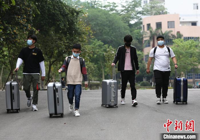 学生推着行李返回宿舍。 朱柳融 摄