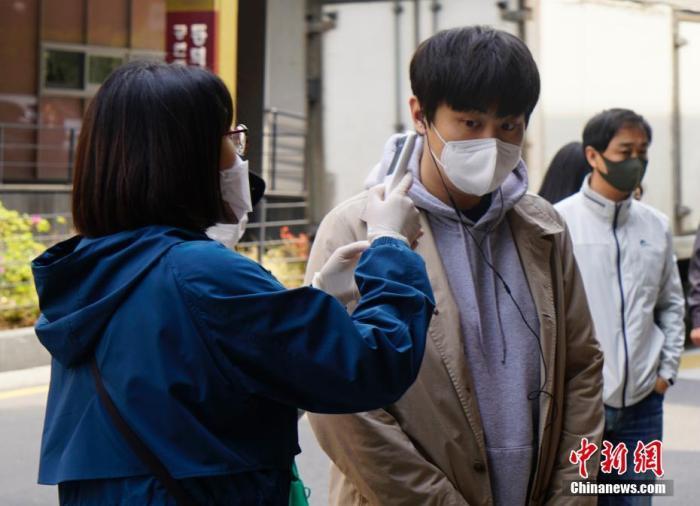 在韩国首尔一投票站,投票者接受体温检测。 中新社记者 曾鼐 摄