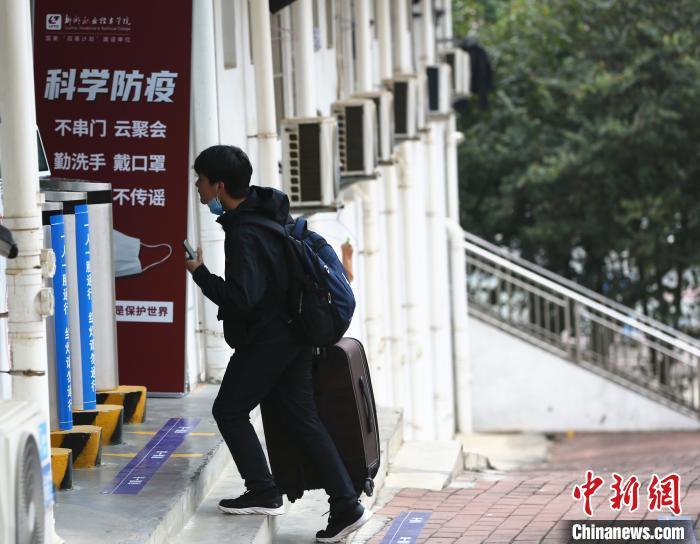 学生拿着行李进入宿舍。 朱柳融 摄