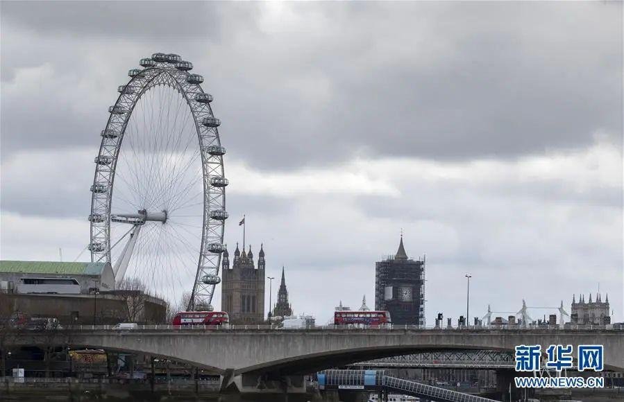 """▲3月30日,在英国伦敦,两辆红色双层巴士从停止转动的""""伦敦眼""""前经过。(新华社记者 韩岩 摄)"""