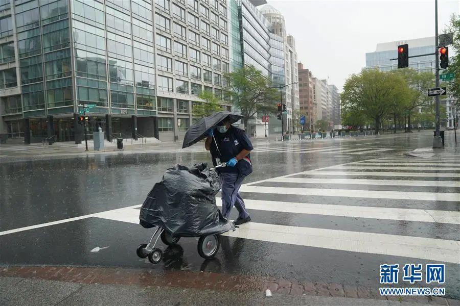 ▲4月13日,在美国都城华盛顿,一名戴着口罩的女子在雨中过马路。(新华社记者 刘杰 摄)