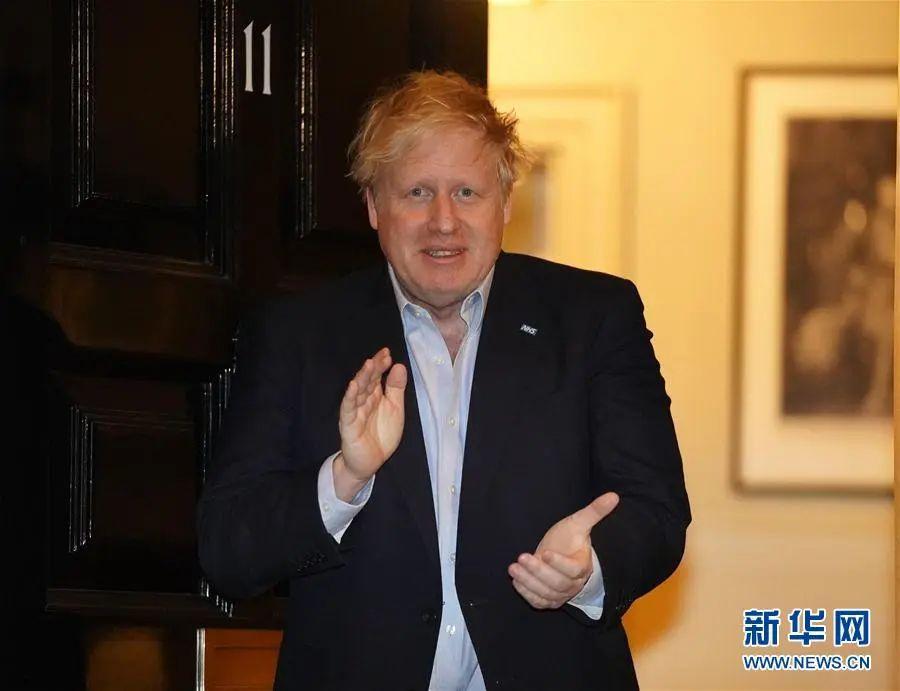 ▲4月2日晚,英国首相约翰逊在伦敦唐宁街11号门口为NHS医护人员鼓掌。(新华社发)