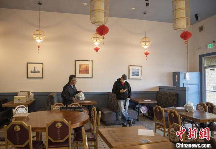 """当地时间3月16日,一名戴口罩的顾客在美国旧金山湾区米尔布雷一家餐馆等餐。这家菜馆从当日开始实行""""无接触取餐"""",顾客网上下单,到店自取食物,饭店也可提供送餐服务。中新社记者 刘关关 摄"""