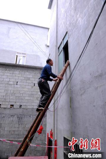 农俊爬上村民自搭楼梯查看灾情。 蒋雪林 摄