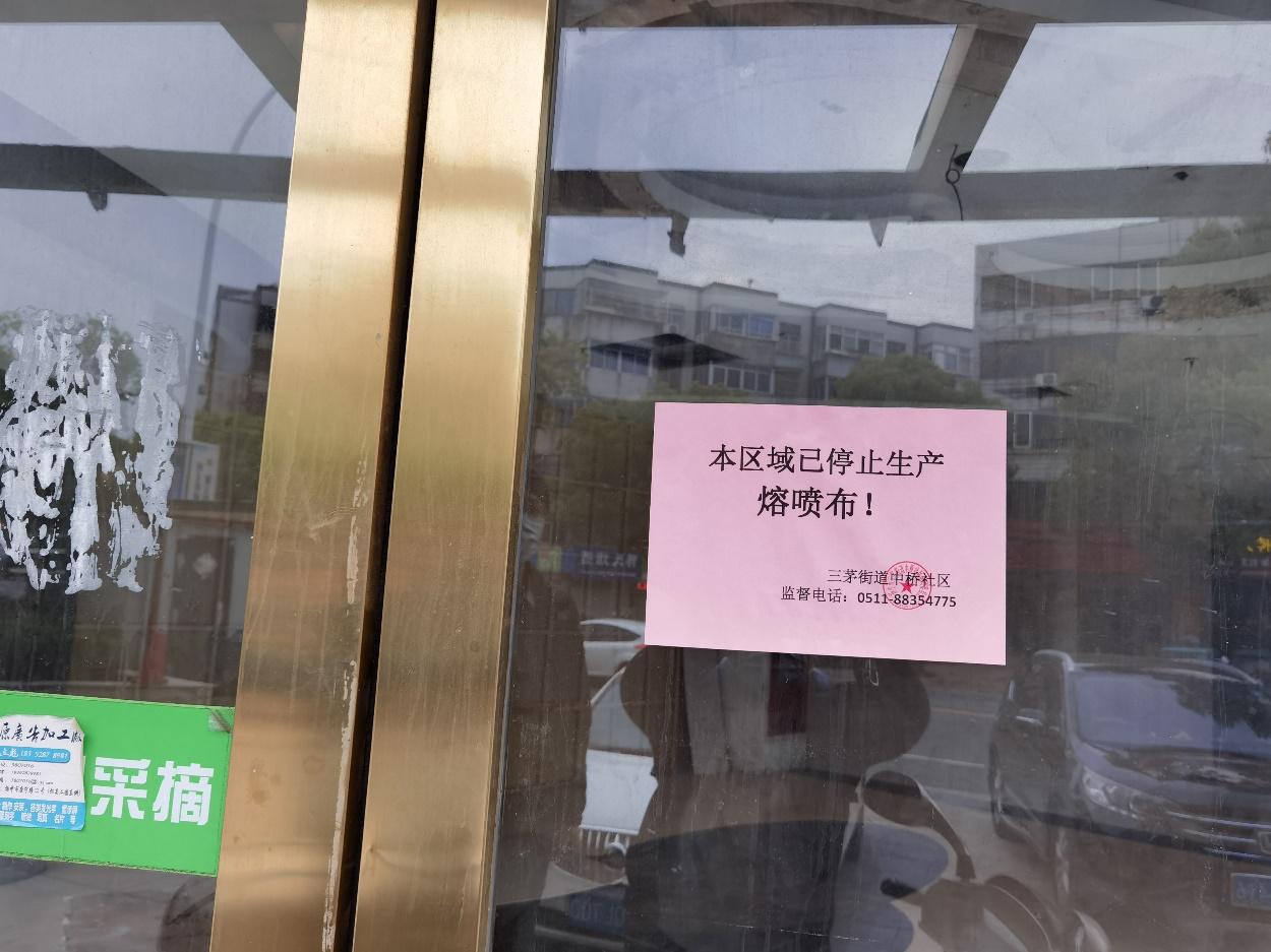 扬中市街道社区贴出关于停产熔喷布的通告。秦枭/拍照