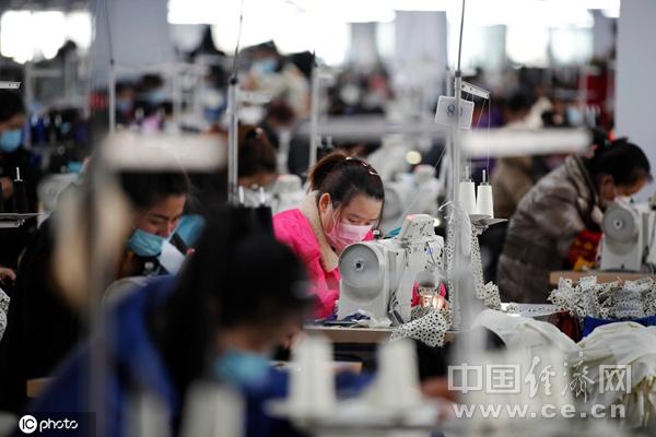 3月3日,江苏泗洪经济开发区一家服装企业的生产车间里,工人正在紧张忙碌。(图片来源:东方IC)