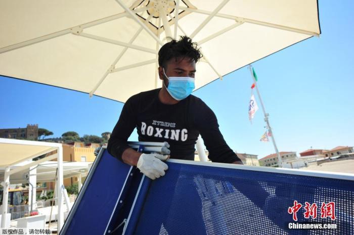 当地时间4月24日,意大利一海滩俱乐部的工人戴着口罩和手套为度假区的重新开业做准备。意大利总理孔特表示,从5月4日开始,该国将正式进入抗疫第二阶段,重启全国经济。
