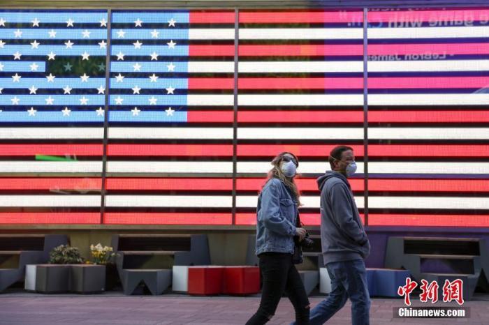 当地时间4月12日,两位戴口罩的市民走过纽约时代广场美国国旗灯箱。中新社记者 廖攀 摄