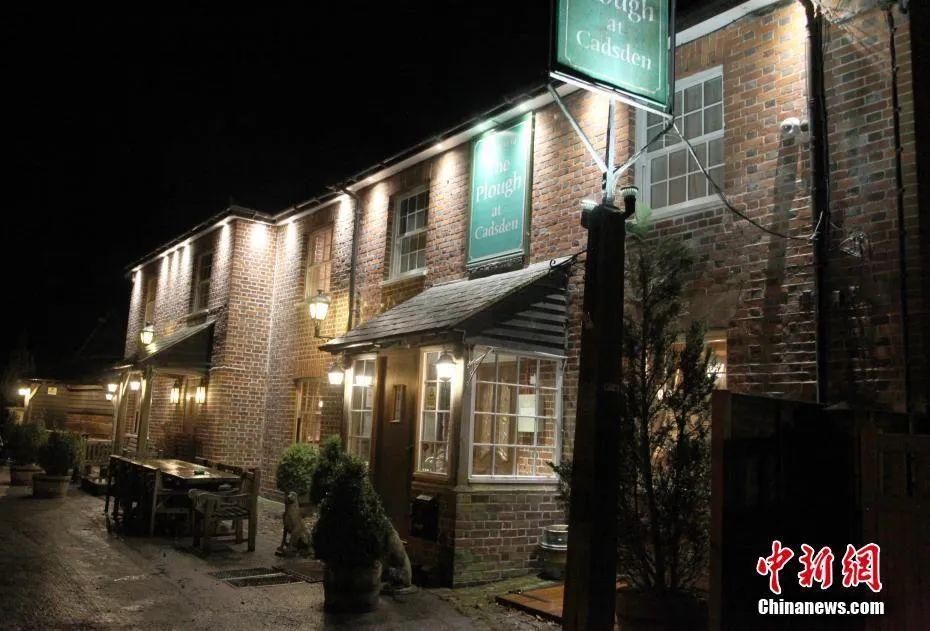 资料图:夜幕中伦敦郊外卡兹顿路边的一个酒吧。中新社记者 张平 摄