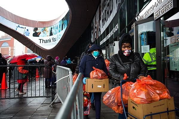 4月24日,在美国纽约布鲁克林区一处食品发放点,人们排队领取食品。新华社 图