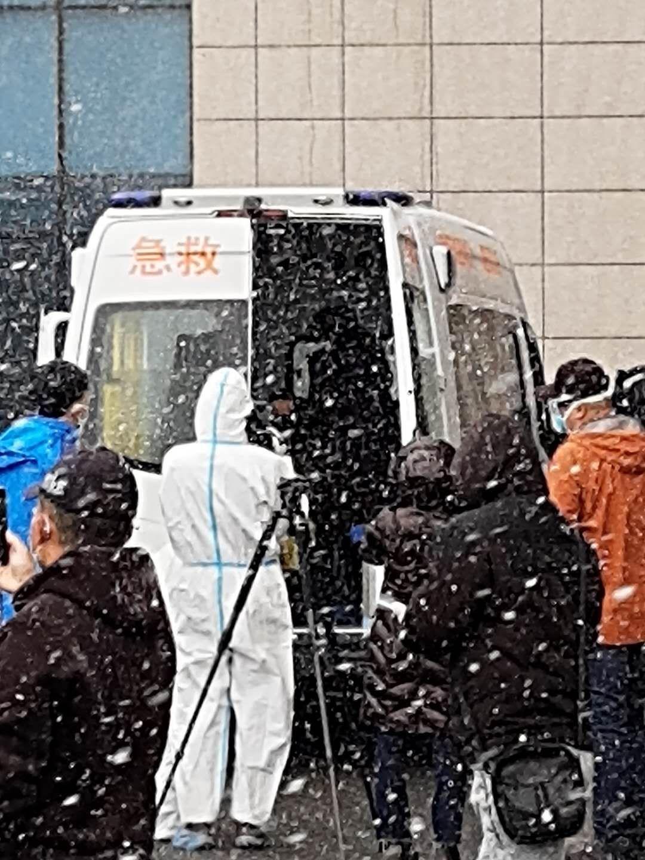医护职员雪中把治愈出院患者奉上负压救护车,转运到定点医院举行会合医学视察