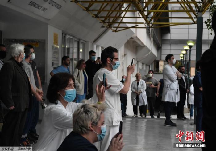 当地时间4月20日,希腊雅典福音医院的医务人员在院子里聆听希腊国家广播交响乐团的音乐会。图为医护人员在欣赏表演。
