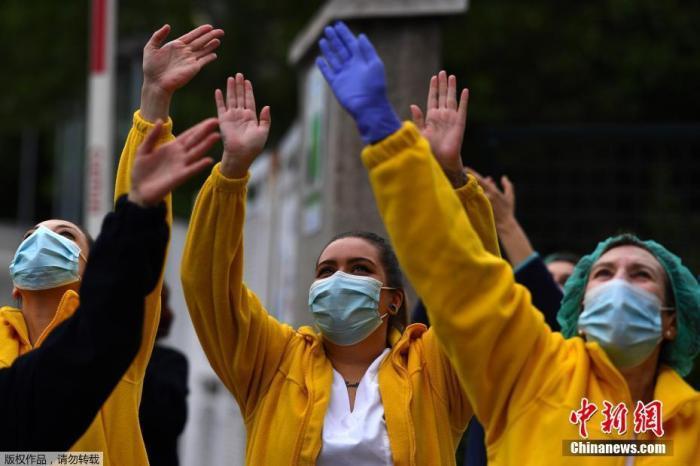 资料图:当地时间4月27日,在西班牙马德里的一家医院外,医护人员在为全国禁闭期间居家隔离的民众们鼓掌欢呼,为他们加油打气。