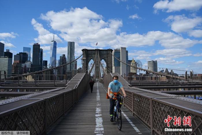 资料图:图为戴着口罩的骑手在纽约布鲁克林大桥上骑行。