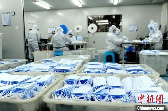 工人有条不紊地赶制出产口罩。张金川 摄
