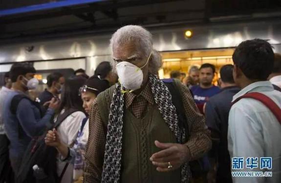 3月13日,在印度新德里一地铁站内,有民众佩戴口罩出行。