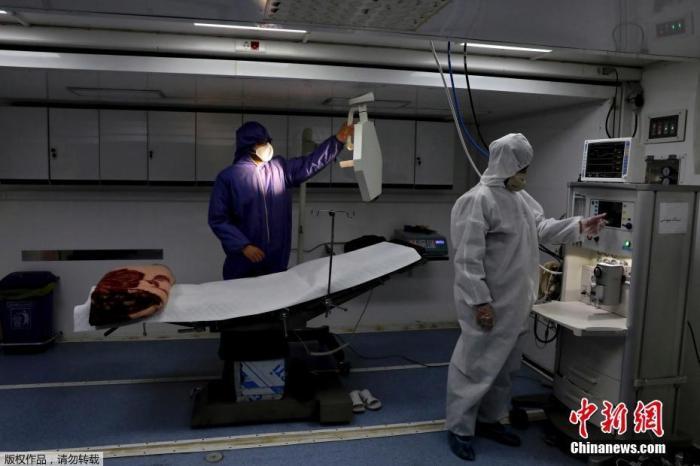 当地时间3月26日,伊朗德黑兰国际展览中心,穿防护服的工作人员在操作医疗设备。据悉,这所方舱医院可以为新冠病毒肺炎患者提供2000张床位。
