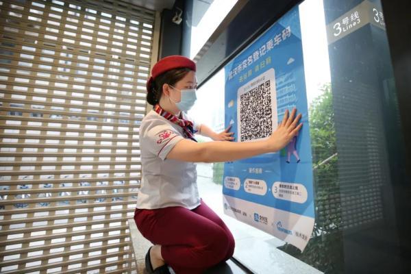 地铁双墩站员工正在为即将打开的出入口张贴二维码。 武汉地铁运营公司供图