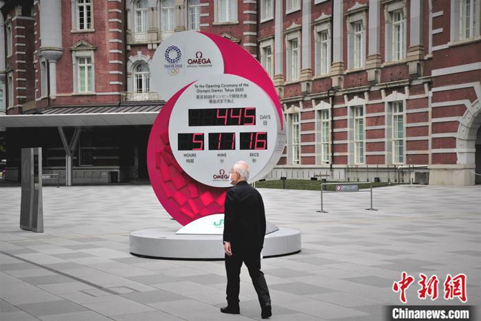 当地时间5月4日,行人走过日本东京车站附近的奥运倒计时电子屏。 中新社记者 吕少威 摄