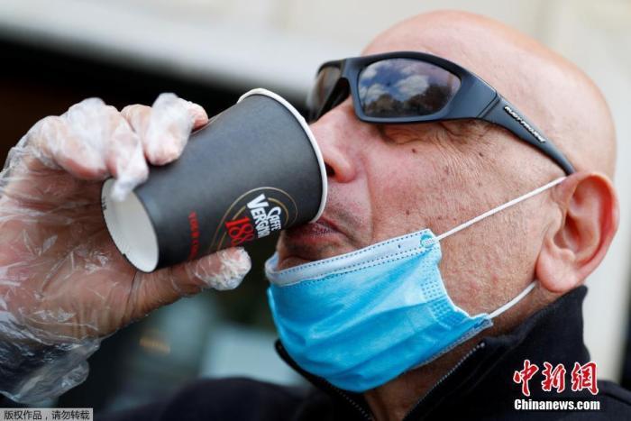 """日前,意大利总理孔特宣布,自当地时间5月4日起,意大利开始解除全国""""封城""""状态。在意大利首都罗马,一名戴着防护口罩和手套的男子正在喝咖啡。"""