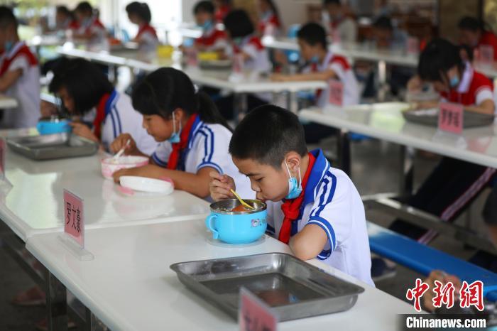 自5月11日起,江西全省中小学生陆续返校学习。为保障学生就餐时的平安,上高县墨山中央小学严酷分批次、错时到食堂就餐,就餐时做到错位分列。陈旗海 摄