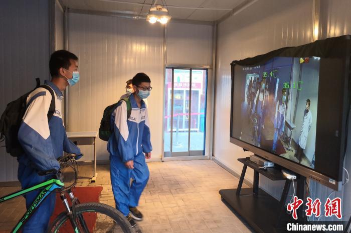 银川唐徕回民中学西校区学生丈量体温正常后入校。李佩珊 摄