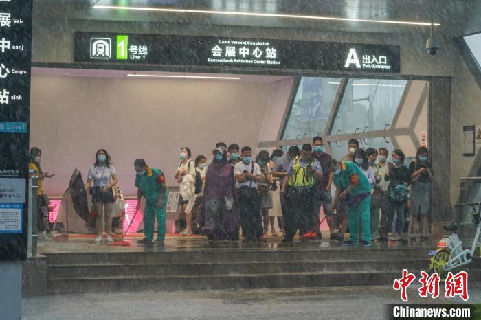 图为市民在地铁口避雨。 陈冠言 摄