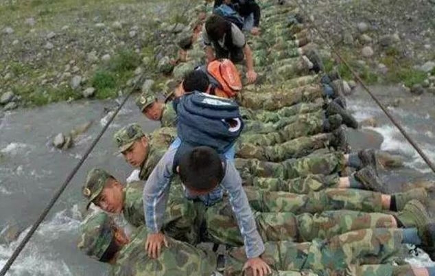 """▲2008年6月,四川省地动灾区彭州市湔江河畔,兵士趴在还没有修完的铁索桥上,构成暂时的""""人桥"""",让小门生们从本身的脊背上爬过。"""