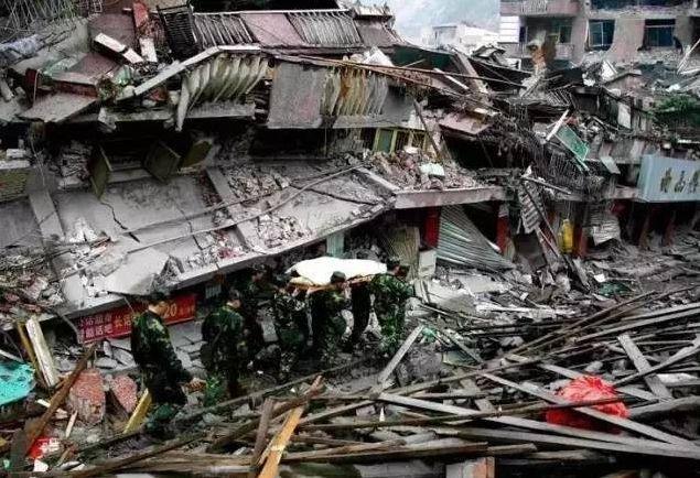 ▲重灾区北川,官兵们抬着一位伤员走在全是瓦砾的大街上。