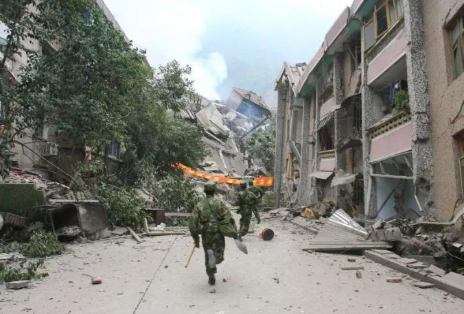 ▲2008年5月13日,四川绵阳北川县,武警兵士奔向衡宇坍塌现场,救济被困伤员。
