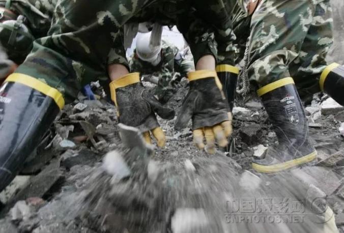 ▲2008年5月16日,汶川县水磨镇的公路被毁,上海公安消防救济队徒手在地动废墟中搜救幸存者。