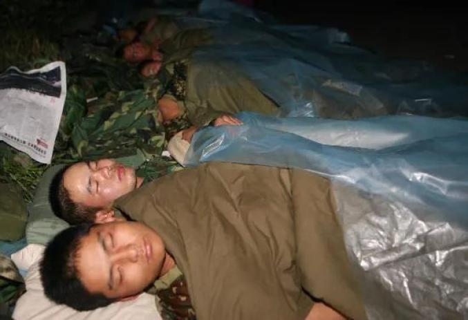 ▲2008年5月15日破晓,加入抗震救灾的济南军区某部兵士在汶川县映秀镇陌头苏息。