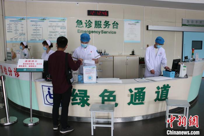 图为柳州市人民医院急诊科男护士陈仕遇在接诊病人。 林馨 摄