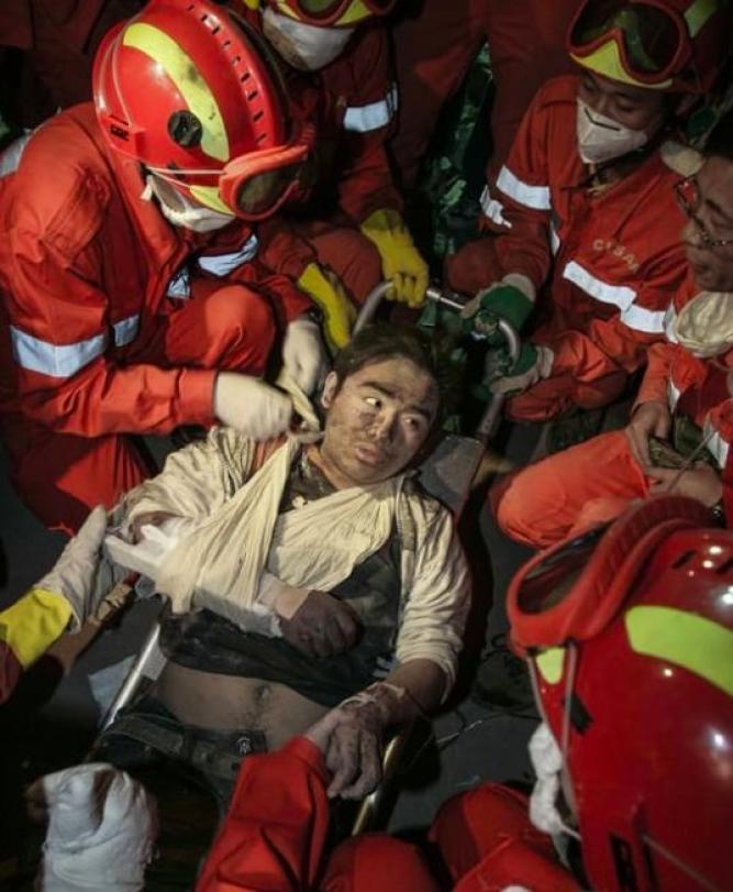 """▲2008年5月15日,绵竹市汉旺东汽中学,灾害已往80个小时,男孩终于被救济职员抬出废墟。他说,""""叔叔,我想喝可乐""""。"""