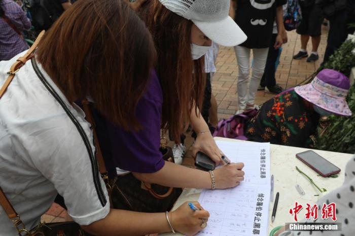 5月13日,香港上水干净工罗伯遭坏人掷砖身亡半周年,过百香港市民自觉到上水北区大礼堂悼念。图为市民签订悼念册。 中新社记者 谢磊 摄