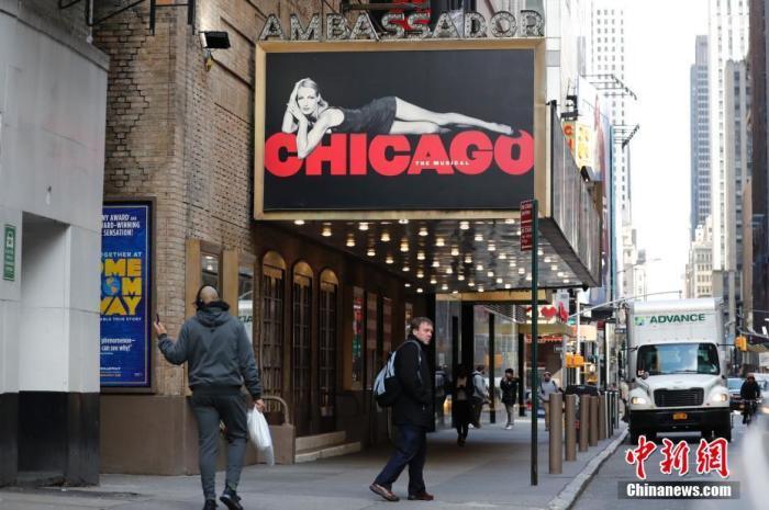 美国纽约百老汇,有人走过关闭的剧院。 中新社记者 廖攀 摄