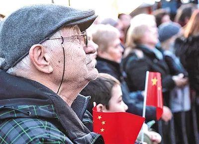 """塞尔维亚当地民众在一场主题为""""塞尔维亚人民永远和中国兄弟在一起""""的音乐会上,手持中国国旗表示对中国的支持。(图/新华社)"""