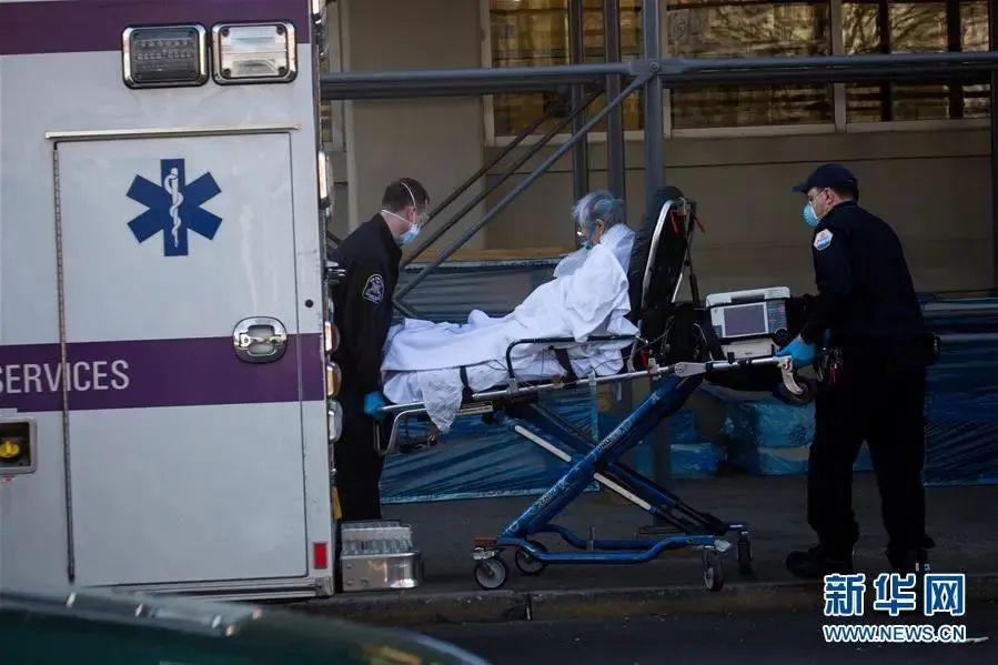 美国纽约,医护职员预备将一名患者送入医院(图源:新华社)