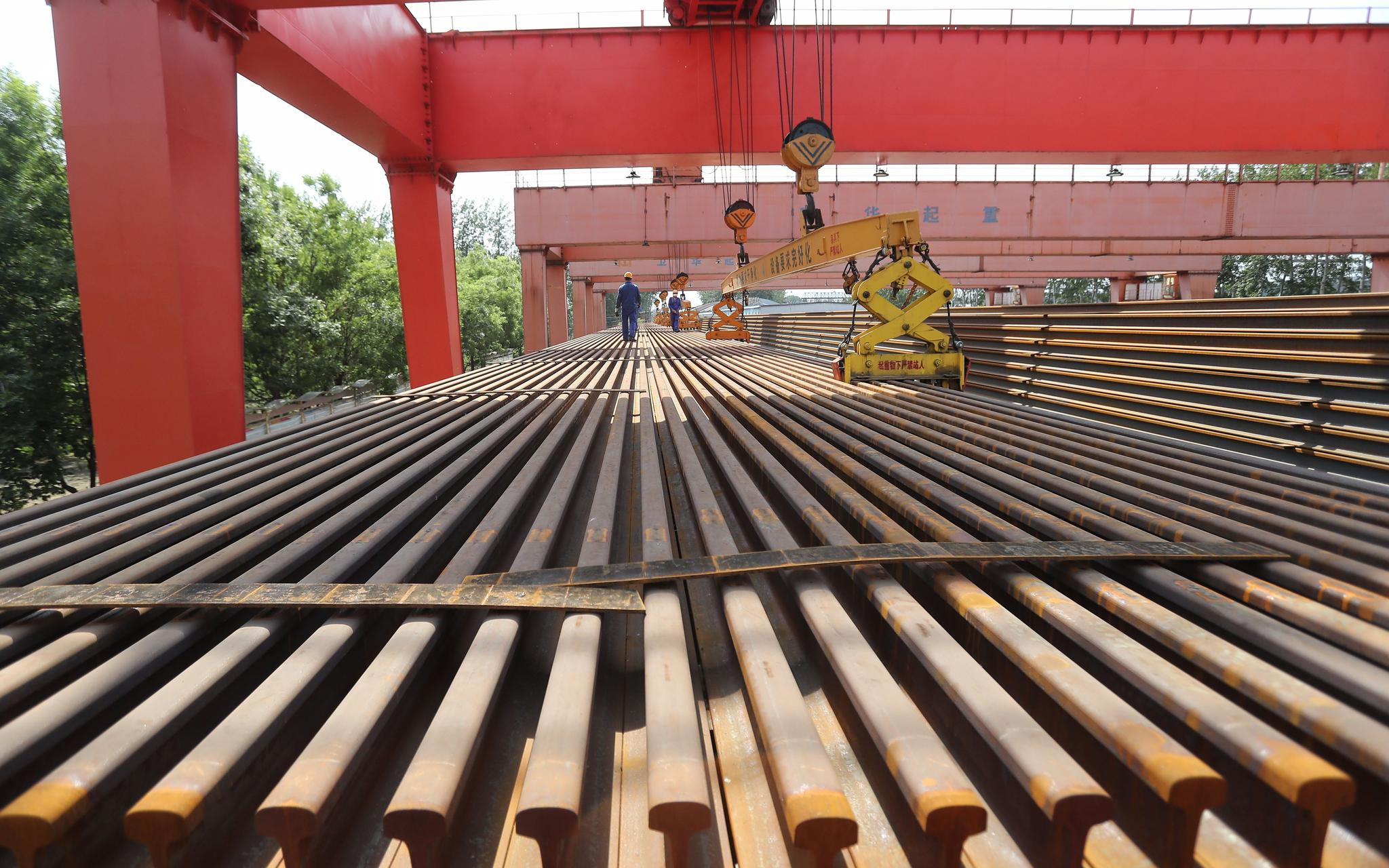 工人准备吊装钢轨。摄影/新京报记者 王贵彬