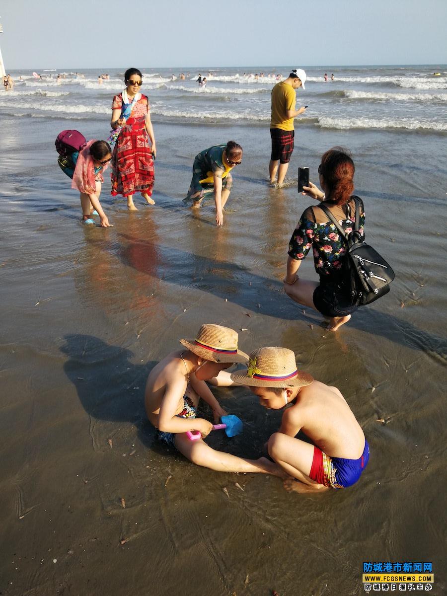 双胞胎少年在江山半岛白浪滩玩沙子