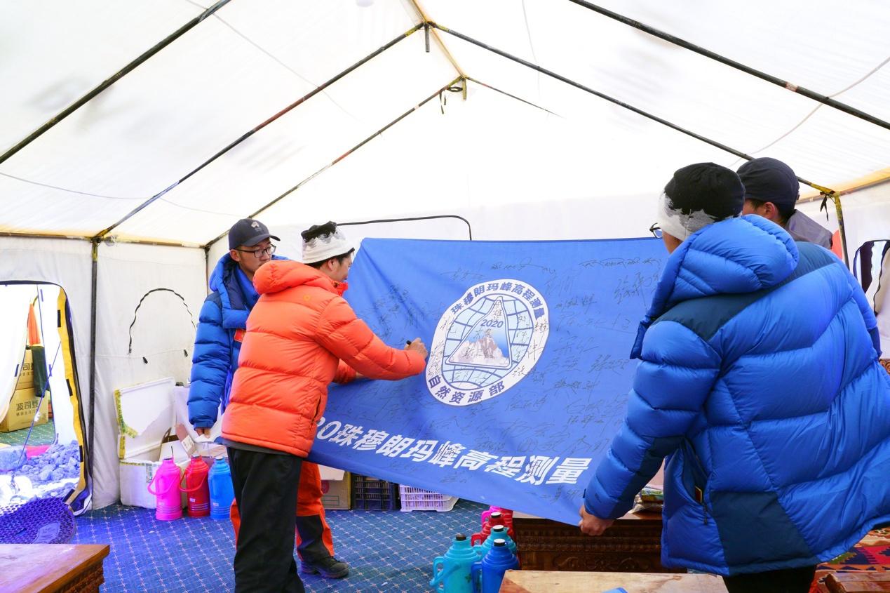 队员们在本次活动旗帜上签名留念。中国登山协会供图 卢明文摄