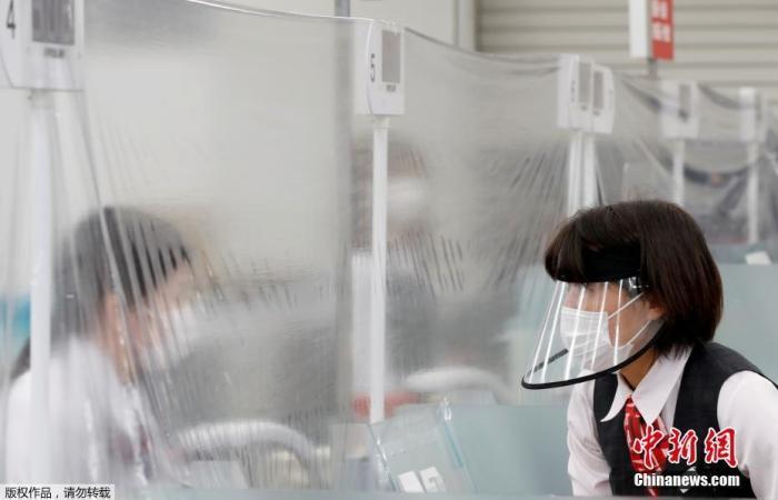 图为日本东京一家银行内,戴口罩的工作人员隔着塑料布与银行柜员交流。