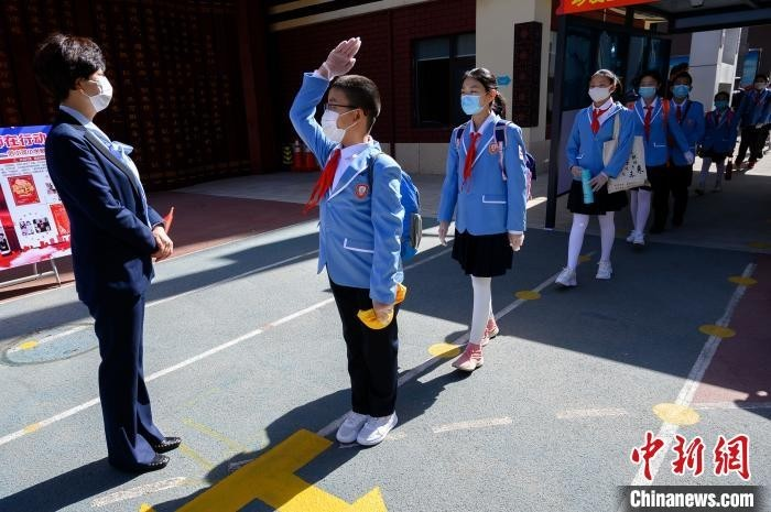 学生们佩戴口罩、间隔排队,次第通过自动测温门,进入校园。 韦亮 摄